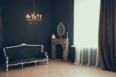 Μαύρο δωμάτιο στο κάστρο με ένα παράθυρο, έναν πολυέλαιο, έναν καναπέ και έναν καθρέφτη και την εστία στοκ φωτογραφία