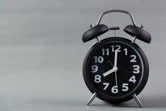Μαύρο εκλεκτής ποιότητας ξυπνητήρι χρώματος στο γκρίζο υπόβαθρο, ξυπνήστε χρόνος Στοκ Φωτογραφίες