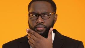 Μαύρο επιχειρησιακό άτομο στα γυαλιά σχετικά με τη γενειάδα, που ψάχνει την καλύτερη επιλογή, απόφαση απόθεμα βίντεο