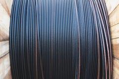 Μαύρο ηλεκτρικό καλώδιο καλωδίων με την ξύλινη σπείρα του ηλεκτρικού καλωδίου Στοκ Φωτογραφία