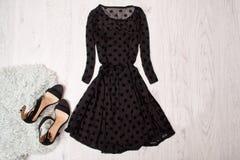 Μαύρο θηλυκό φόρεμα με τα μακριά μανίκια και τα μαύρα παπούτσια σε ένα ξύλινο υπόβαθρο Μοντέρνη έννοια, τοπ άποψη στοκ εικόνες με δικαίωμα ελεύθερης χρήσης