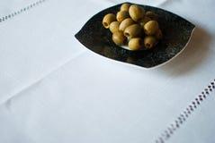 Μαύρο διαμορφωμένο πιάτο με τις ελιές στο άσπρο τραπεζομάντιλο Στοκ Εικόνες