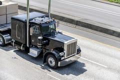Μαύρο ισχυρό μεγάλο κλασικό ημι φορτηγό εγκαταστάσεων γεώτρησης που μεταφέρει το φορτίο στο επίπεδο ημι ρυμουλκό κρεβατιών που κι στοκ φωτογραφία με δικαίωμα ελεύθερης χρήσης