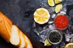 Μαύρο και κόκκινο χαβιάρι στα κύπελλα γυαλιού στον πάγο στο μαύρο backgrou Στοκ εικόνα με δικαίωμα ελεύθερης χρήσης