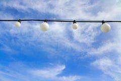 Μαύρο καλώδιο με τις άσπρες λάμπες φωτός ενάντια σε έναν μπλε ουρανό με τα σύννεφα στοκ φωτογραφία