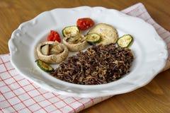 Μαύρο καναδικό ρύζι που εξυπηρετείται με τα μανιτάρια, τις ντομάτες και τα κολοκύθια Στοκ φωτογραφία με δικαίωμα ελεύθερης χρήσης