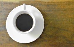 μαύρο καυτό φλυτζάνι καφέ στο πιάτο στον πίνακα στοκ εικόνα με δικαίωμα ελεύθερης χρήσης