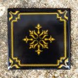 Μαύρο κεραμίδι με μια χρυσή διακόσμηση, τετραγωνική μορφή Παλαιό επίστρωμα στοκ φωτογραφίες