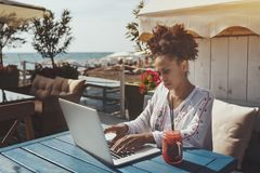 Μαύρο κορίτσι που χρησιμοποιεί το lap-top στον καφέ κοντά στη θάλασσα στοκ φωτογραφίες