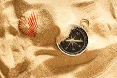 Μαύρο κοχύλι πυξίδων και θάλασσας στην άμμο Στοκ εικόνα με δικαίωμα ελεύθερης χρήσης