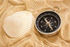 Μαύρο κοχύλι πυξίδων και θάλασσας στην άμμο Στοκ φωτογραφία με δικαίωμα ελεύθερης χρήσης