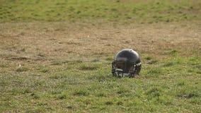 Μαύρο κράνος ποδοσφαίρου που βρίσκεται στην πίσσα, επαγγελματικά αθλήματα, υπαίθριες δραστηριότητες απόθεμα βίντεο