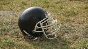 Μαύρο κράνος που βρίσκεται στη χλόη στην πίσσα, σύμβολο του παιχνιδιού αμερικανικού ποδοσφαίρου, αθλητισμός απόθεμα βίντεο