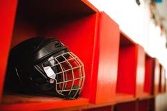 Μαύρο κράνος προστασίας χόκεϋ με το κλουβί στο κόκκινο ράφι απεικόνιση αποθεμάτων
