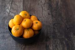 Μαύρο κύπελλο satsuma των πορτοκαλιών σε έναν αγροτικό ξύλινο πίνακα στοκ φωτογραφίες