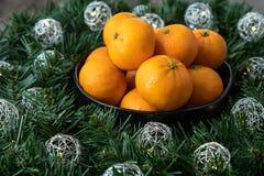 Μαύρο κύπελλο satsuma των πορτοκαλιών σε ένα στεφάνι Χριστουγέννων με τα ασημένια φω'τα σφαιρών στοκ φωτογραφίες