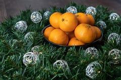 Μαύρο κύπελλο satsuma των πορτοκαλιών σε ένα στεφάνι Χριστουγέννων με τα ασημένια φω'τα σφαιρών στοκ φωτογραφία με δικαίωμα ελεύθερης χρήσης
