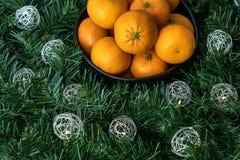 Μαύρο κύπελλο satsuma των πορτοκαλιών σε ένα στεφάνι Χριστουγέννων με τα ασημένια φω'τα σφαιρών στοκ φωτογραφίες με δικαίωμα ελεύθερης χρήσης