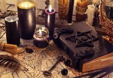 Μαύρο μαγικό βιβλίο με τα μαύρα κεριά και το έγγραφο δαιμόνων Στοκ Εικόνες