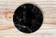Μαύρο μαρμάρινο πιάτο που τοποθετείται στο ξύλο Στοκ εικόνες με δικαίωμα ελεύθερης χρήσης