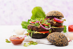 Μαύρο μεγάλο σάντουιτς - μαύρο χάμπουργκερ με juicy burger βόειου κρέατος, το τυρί, την ντομάτα, και το κόκκινο κρεμμύδι Στοκ εικόνα με δικαίωμα ελεύθερης χρήσης
