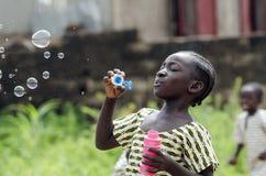 Μαύρο νέο όμορφο κορίτσι που έχει τη διασκέδαση που φυσά υπαίθρια το σαπούνι bubb Στοκ εικόνα με δικαίωμα ελεύθερης χρήσης