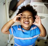 Μαύρο παιδί που χαμογελά στο δωμάτιο πλυντηρίων στοκ φωτογραφίες