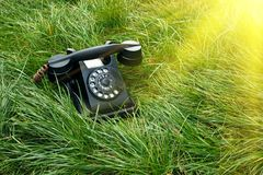 Μαύρο παλαιό αναδρομικό τηλέφωνο στη χλόη με την ηλιοφάνεια Στοκ φωτογραφία με δικαίωμα ελεύθερης χρήσης