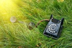 Μαύρο παλαιό αναδρομικό τηλέφωνο στη χλόη με την ηλιοφάνεια Στοκ Φωτογραφία