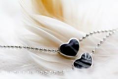 Μαύρο περιδέραιο διαμαντιών μορφής καρδιών στο φτερό στοκ φωτογραφίες