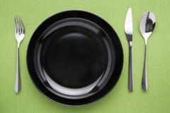 Μαύρο πιάτο στο επιτραπέζιο μαχαίρι και το κουτάλι δικράνων Στοκ Εικόνες