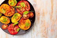 Μαύρο πιάτο της σαλάτας με τις τεμαχισμένες ντομάτες παλαιές στον ξύλινο πίνακα Στοκ φωτογραφία με δικαίωμα ελεύθερης χρήσης