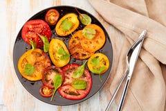 Μαύρο πιάτο της σαλάτας με τις τεμαχισμένες ντομάτες που εξυπηρετούνται στον ξύλινο πίνακα Στοκ εικόνα με δικαίωμα ελεύθερης χρήσης