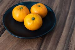 Μαύρο πιάτο satsuma των πορτοκαλιών σε έναν αγροτικό ξύλινο πίνακα στοκ εικόνα με δικαίωμα ελεύθερης χρήσης