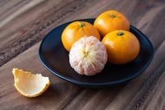 Μαύρο πιάτο satsuma των πορτοκαλιών σε έναν αγροτικό ξύλινο πίνακα στοκ εικόνες