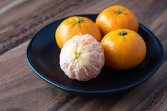 Μαύρο πιάτο satsuma των πορτοκαλιών σε έναν αγροτικό ξύλινο πίνακα στοκ εικόνα