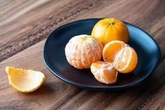 Μαύρο πιάτο satsuma των πορτοκαλιών σε έναν αγροτικό ξύλινο πίνακα στοκ φωτογραφία