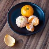 Μαύρο πιάτο satsuma των πορτοκαλιών σε έναν αγροτικό ξύλινο πίνακα στοκ φωτογραφία με δικαίωμα ελεύθερης χρήσης