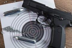 Μαύρο πνευματικό πιστόλι (αεροβόλο πιστόλι), δύο κύλινδροι αερίου, ένας στόχος α Στοκ Εικόνες