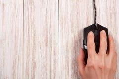 Μαύρο ποντίκι υπολογιστών με ένα χέρι σε ένα άσπρο ξύλινο υπόβαθρο με το διάστημα αντιγράφων για το κείμενό σας Τοπ όψη Στοκ φωτογραφία με δικαίωμα ελεύθερης χρήσης
