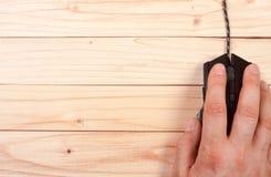 Μαύρο ποντίκι υπολογιστών με ένα χέρι σε ένα ελαφρύ ξύλινο υπόβαθρο με το διάστημα αντιγράφων για το κείμενό σας Τοπ όψη Στοκ φωτογραφία με δικαίωμα ελεύθερης χρήσης