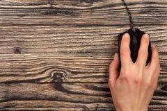 Μαύρο ποντίκι υπολογιστών με ένα χέρι σε ένα μαύρο ξύλινο υπόβαθρο με το διάστημα αντιγράφων για το κείμενό σας Τοπ όψη Στοκ εικόνα με δικαίωμα ελεύθερης χρήσης