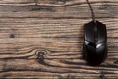 Μαύρο ποντίκι υπολογιστών σε ένα μαύρο ξύλινο υπόβαθρο με το διάστημα αντιγράφων για το κείμενό σας Τοπ όψη Στοκ Εικόνες
