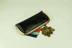 Μαύρο πορτοφόλι γυναικών ` s δέρματος δίπλα στο οποίο χρωματισμένες κάρτες έκπτωσης στοκ εικόνα
