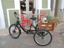 Μαύρο ποδήλατο και δύο κόκκινες έδρες μιας γοητείας Café σε μια πόλη Nafplio Στοκ φωτογραφία με δικαίωμα ελεύθερης χρήσης