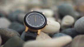 Μαύρο ρολόι πολυτέλειας με το μαύρο λουρί ρολογιών στις πέτρες παραλιών απόθεμα βίντεο