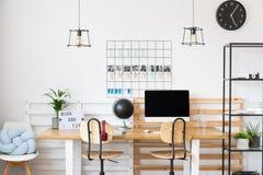Μαύρο ρολόι στο άσπρο γραφείο Στοκ εικόνα με δικαίωμα ελεύθερης χρήσης