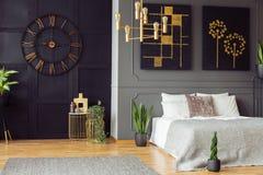 Μαύρο ρολόι, χρυσός πολυέλαιος, έργα ζωγραφικής και άσπρο κρεβάτι σε ένα κομψό εσωτερικό κρεβατοκάμαρων Πραγματική φωτογραφία στοκ εικόνες