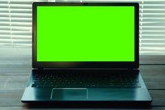 Μαύρο σημειωματάριο σε έναν πίνακα με την πράσινη οθόνη Στοκ Εικόνες