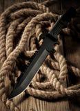 Μαύρο στρατιωτικό μαχαίρι αγώνα στον ξύλινο πίνακα Στοκ Εικόνες
